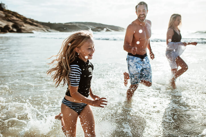 mother and father running daughter through shallow ocean water