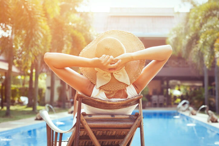 woman relaxing in lounge by pool with hands behind head