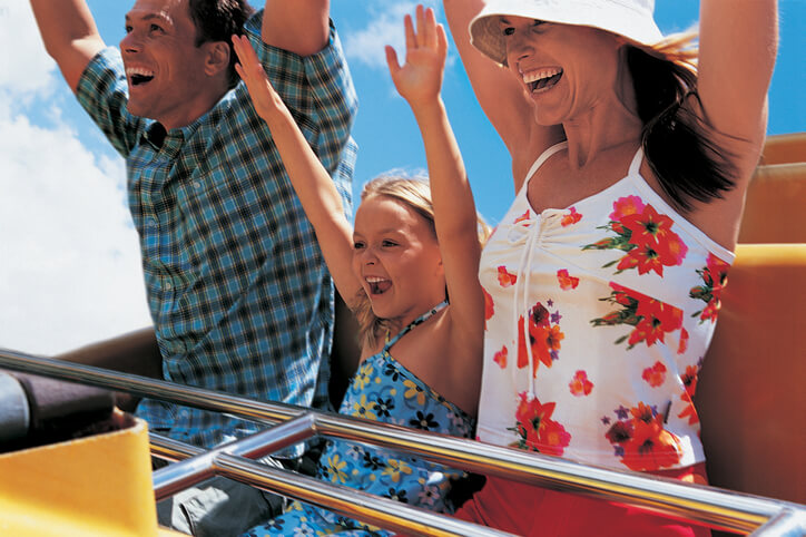 mother and father with daughter holding their arms up riding rollercoaster